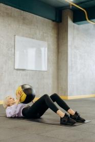 女人抱球躺在瑜伽垫上运动图片